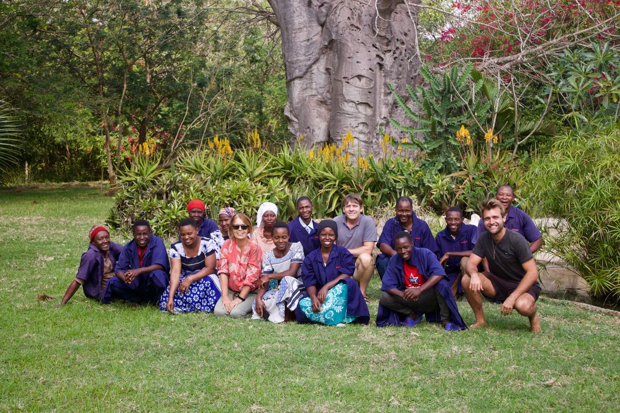 Staff of Mbuyuni Farm in front of a baobab tree