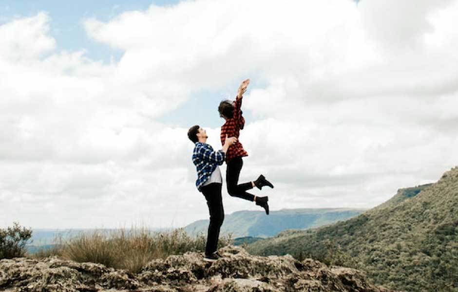 Couple jumping together with mountain view