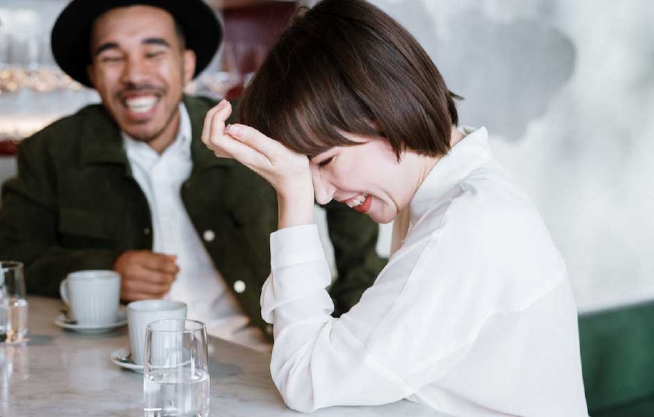 A man and woman laughing together.