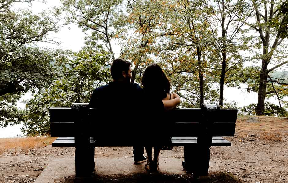 A couple sat on a bench together
