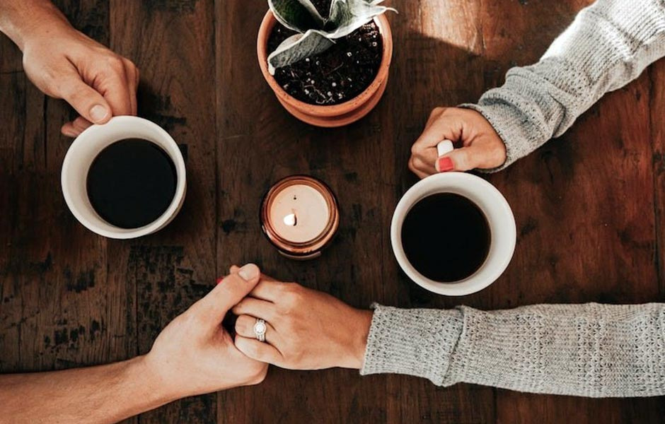 A couple holding hands over a wooden table having a coffee