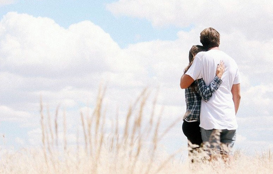 A couple hugging and stood in a field
