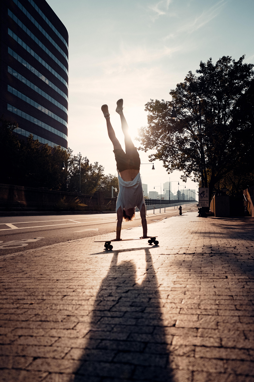 Sage Delaney doing a handstand on a longboard skateboard