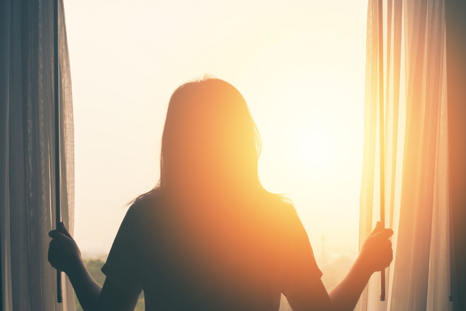 Wake up tired: The silhouette of a woman opening her curtains as the sun rises