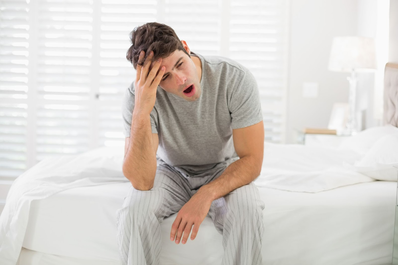Wake up tired: A yawning man sits on the edge of his bed