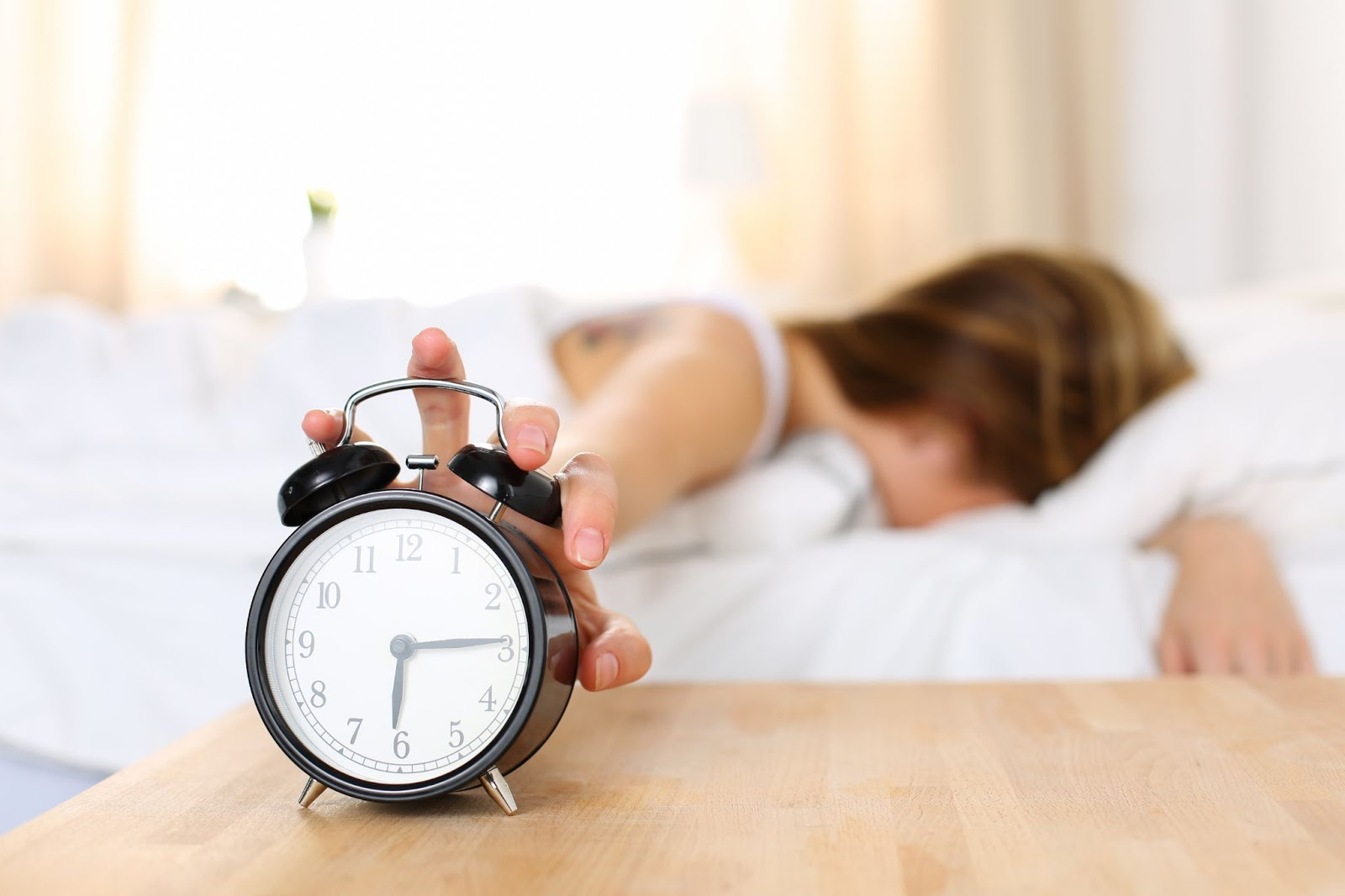 Sleep inertia: A woman reaches to turn off her alarm clock