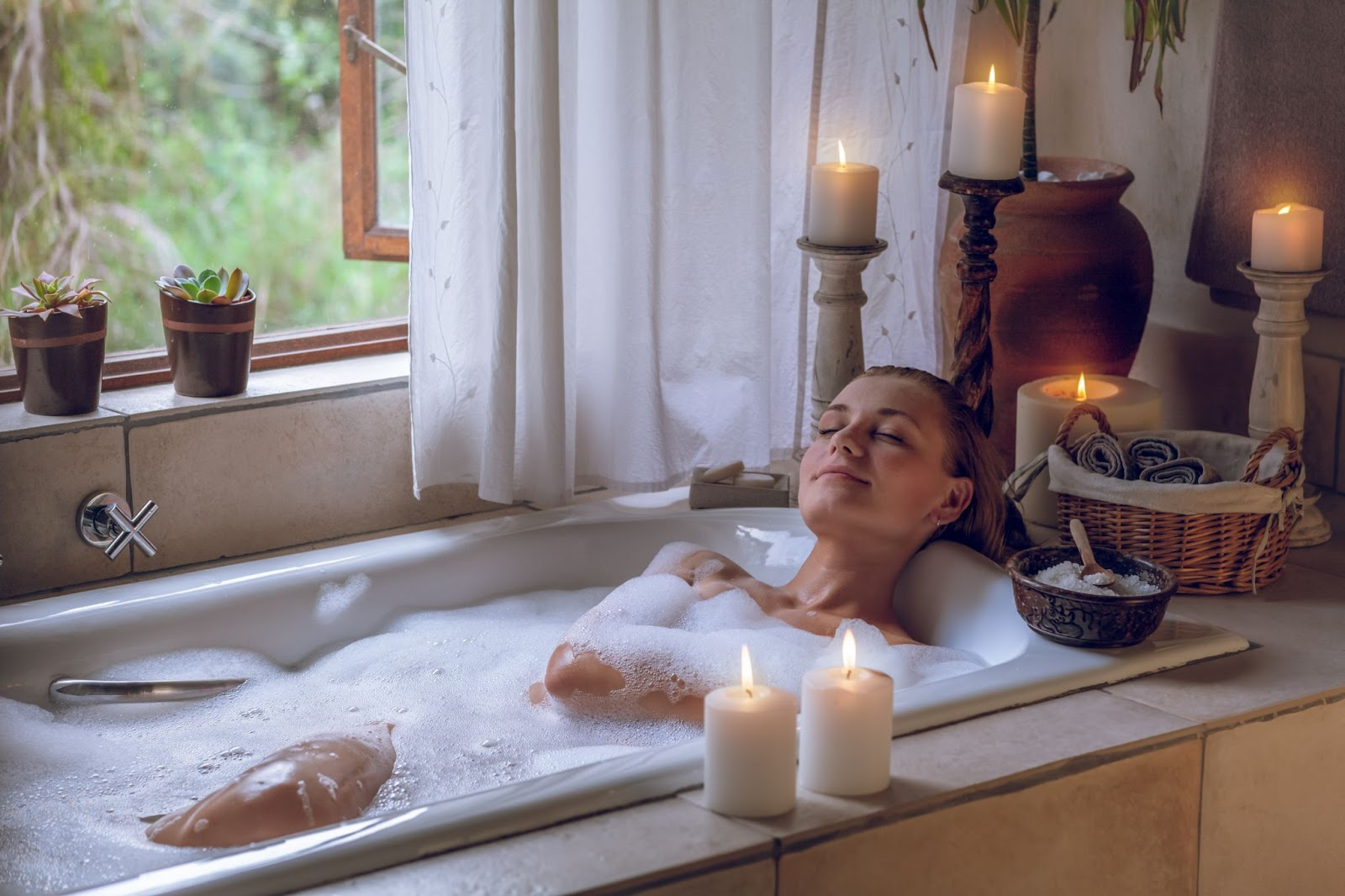 A woman relaxes in a bathtub surrounded by candles