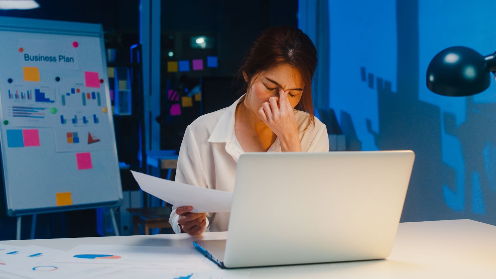 Sleep procrastination: A woman closes her eyes while sitting in her office late at night