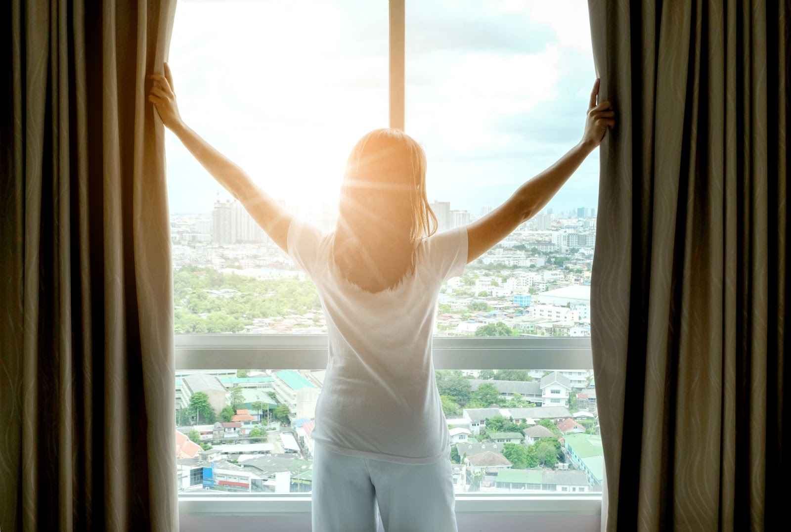A woman opens her curtains to see the sunshine in the morning