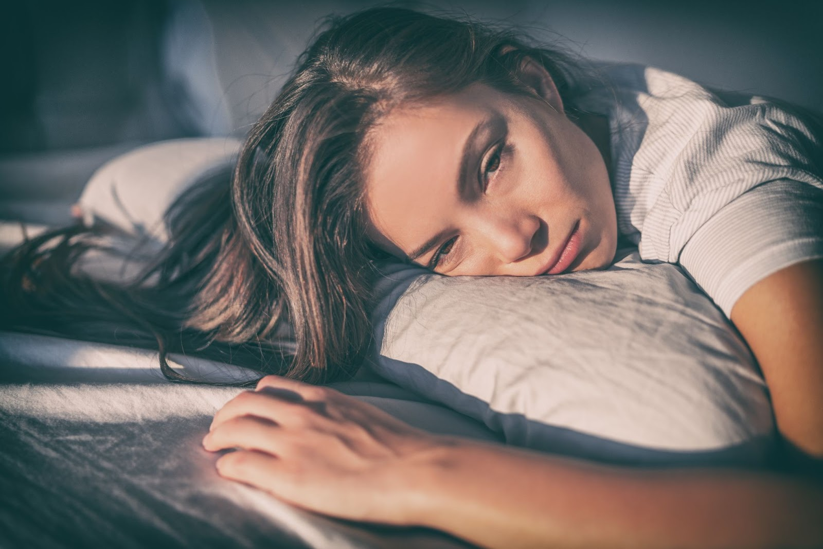 Sleeping during the day: A woman lies in bed looking tired