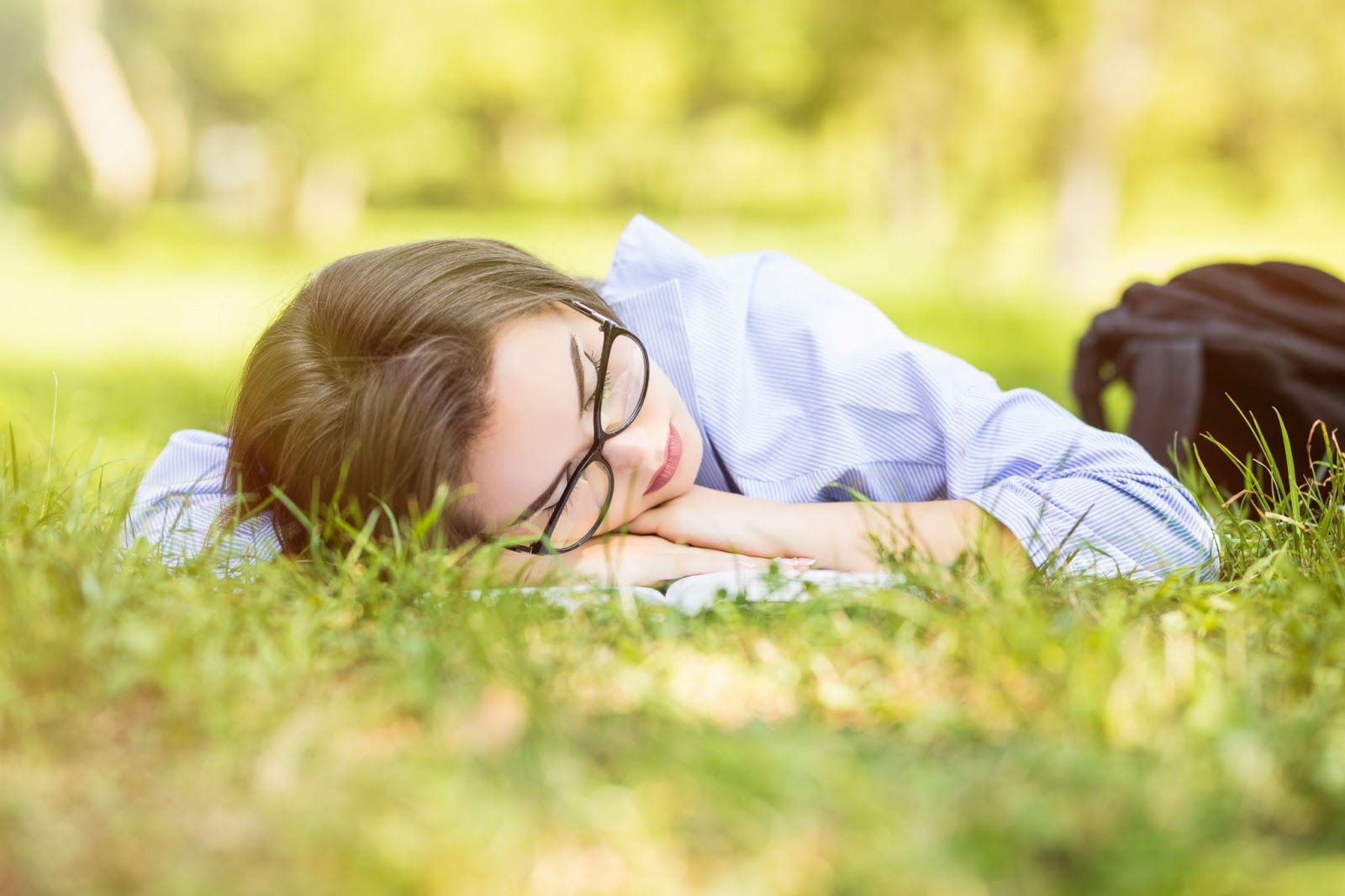 A woman naps outside in the grass