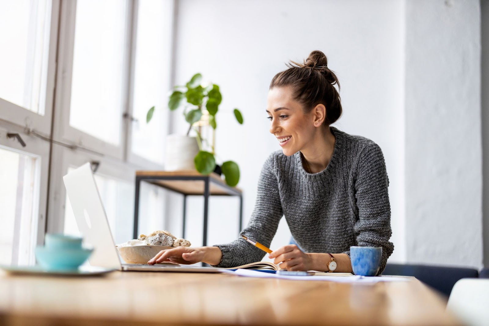 A smiling woman works on her laptop