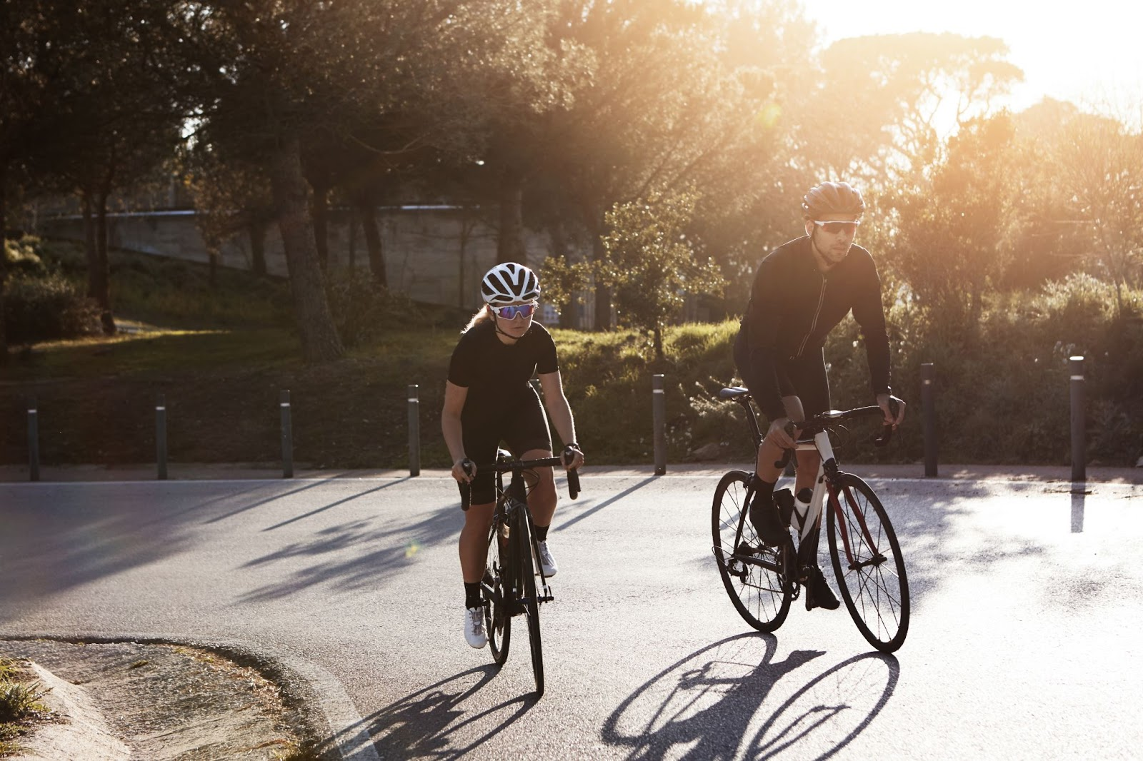 Two people ride bikes in the morning