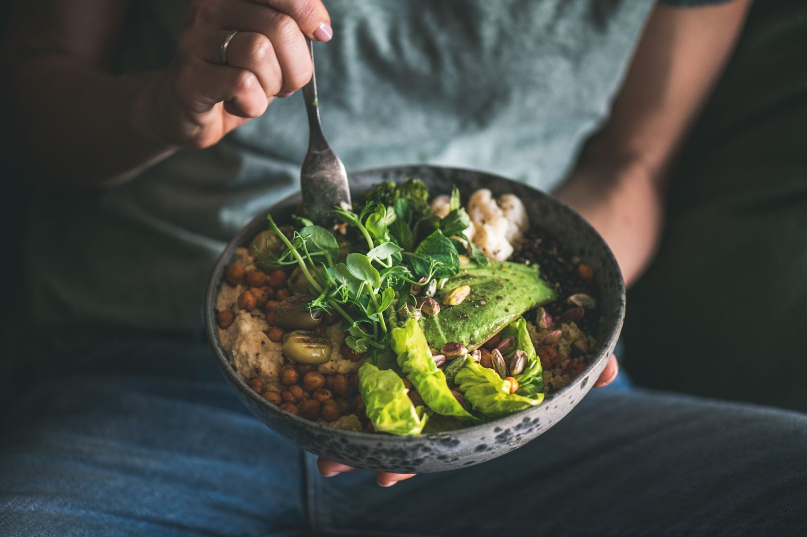 A person puts a fork in a bowl of healthy food