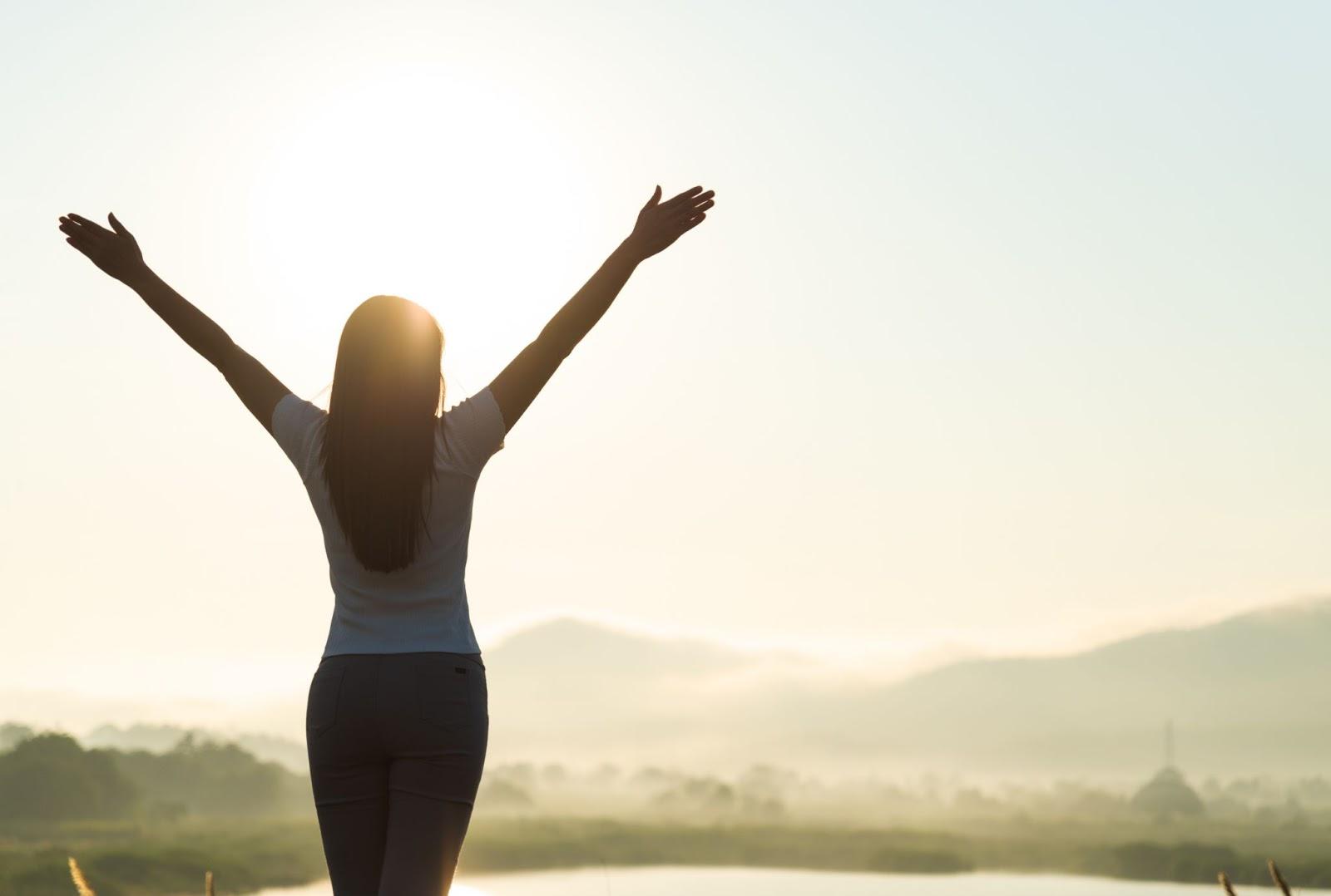Natural energy: A woman raises her hands toward the rising sun
