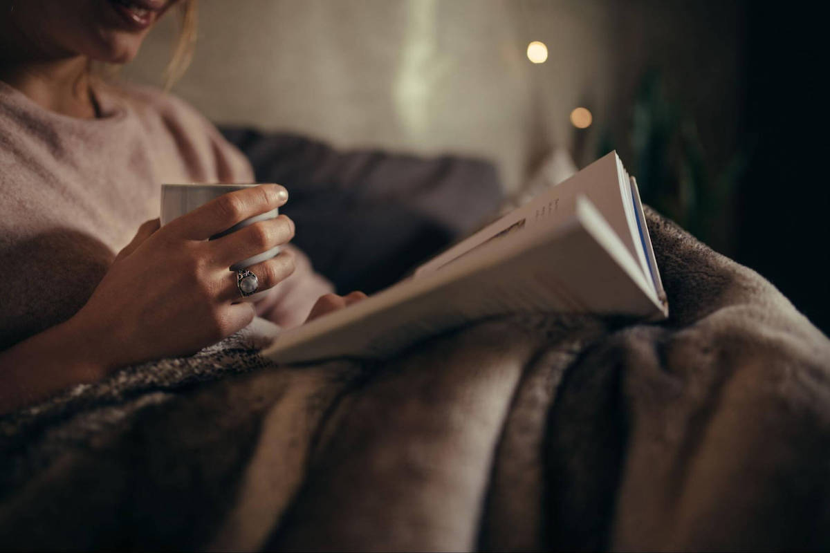 Can you catch up on sleep: A woman reads a book and drinks tea before bed