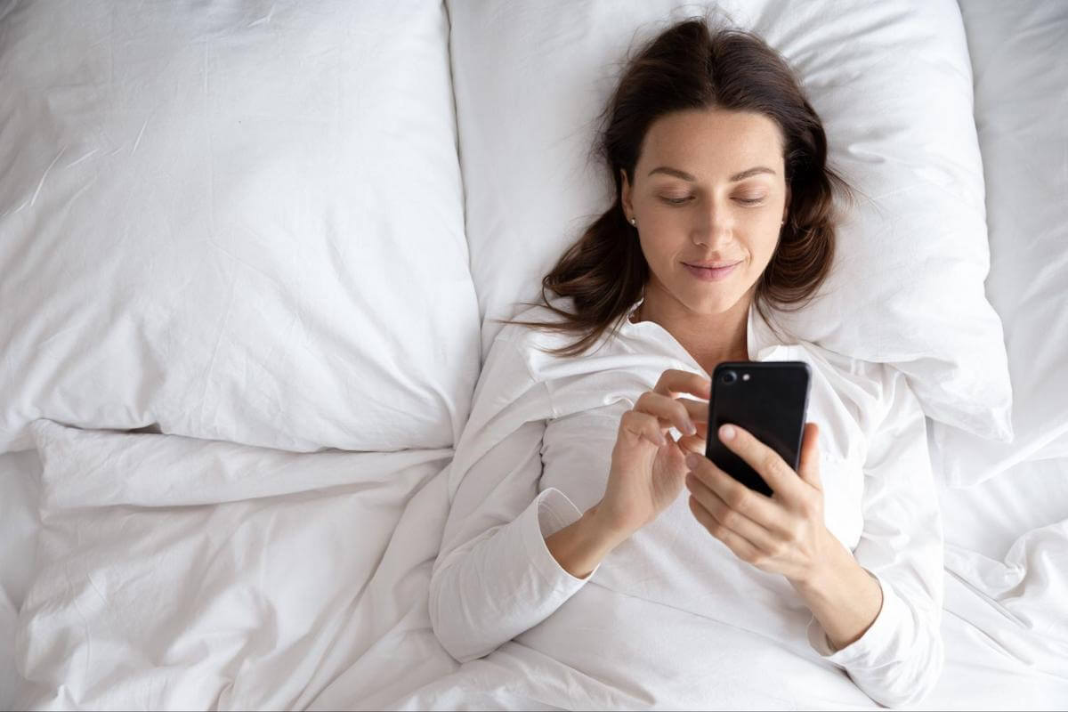 How long does it take to recover from sleep deprivation: A woman uses her phone while in bed