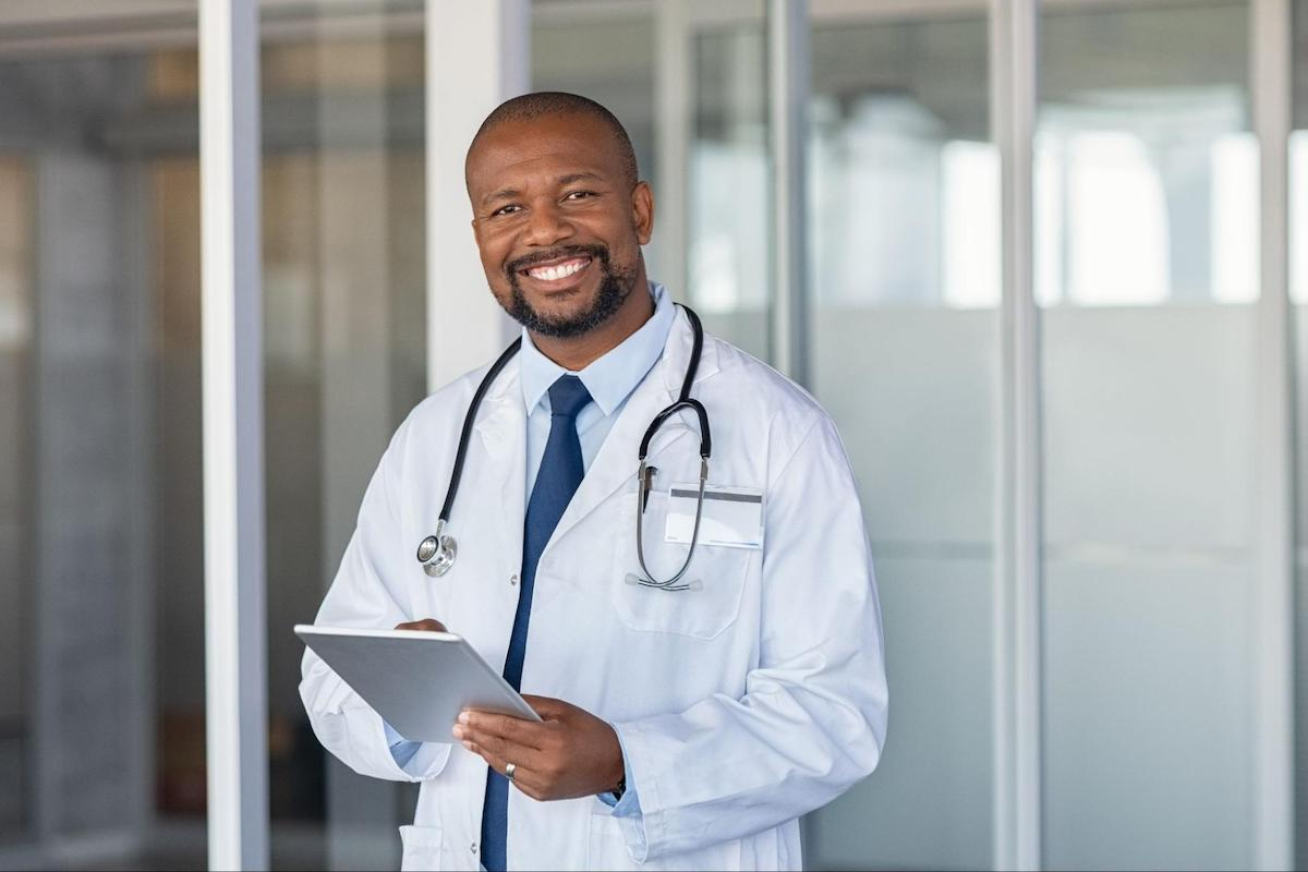 A doctor smiles while holding a tablet