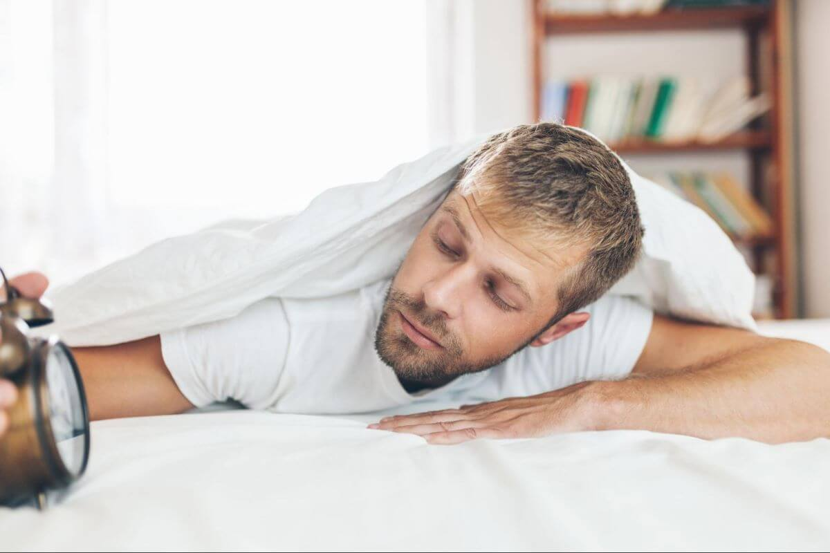 getting out of bed: Man looking at his alarm clock while lying in bed