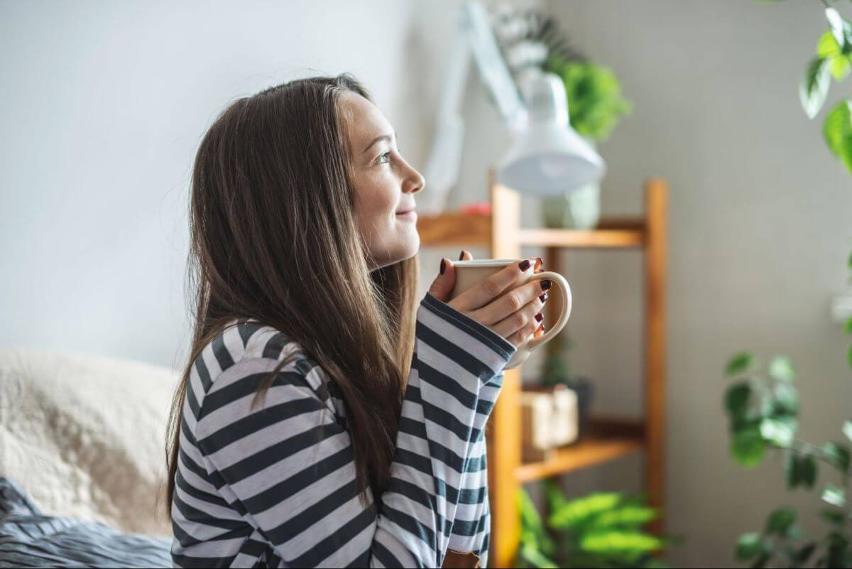 Smiling woman holding a cup of coffee while sitting on the couch