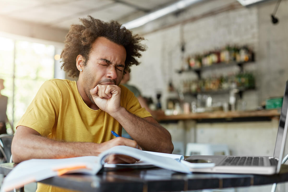 how long can you go without sleep: Man yawning with his eyes closed while working