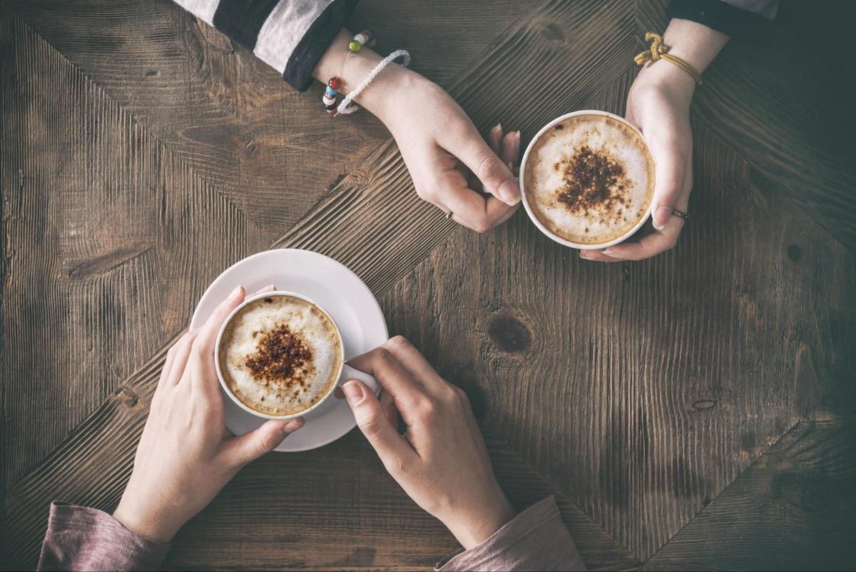 Top view of two people holding a cup of coffee on a wooden surface