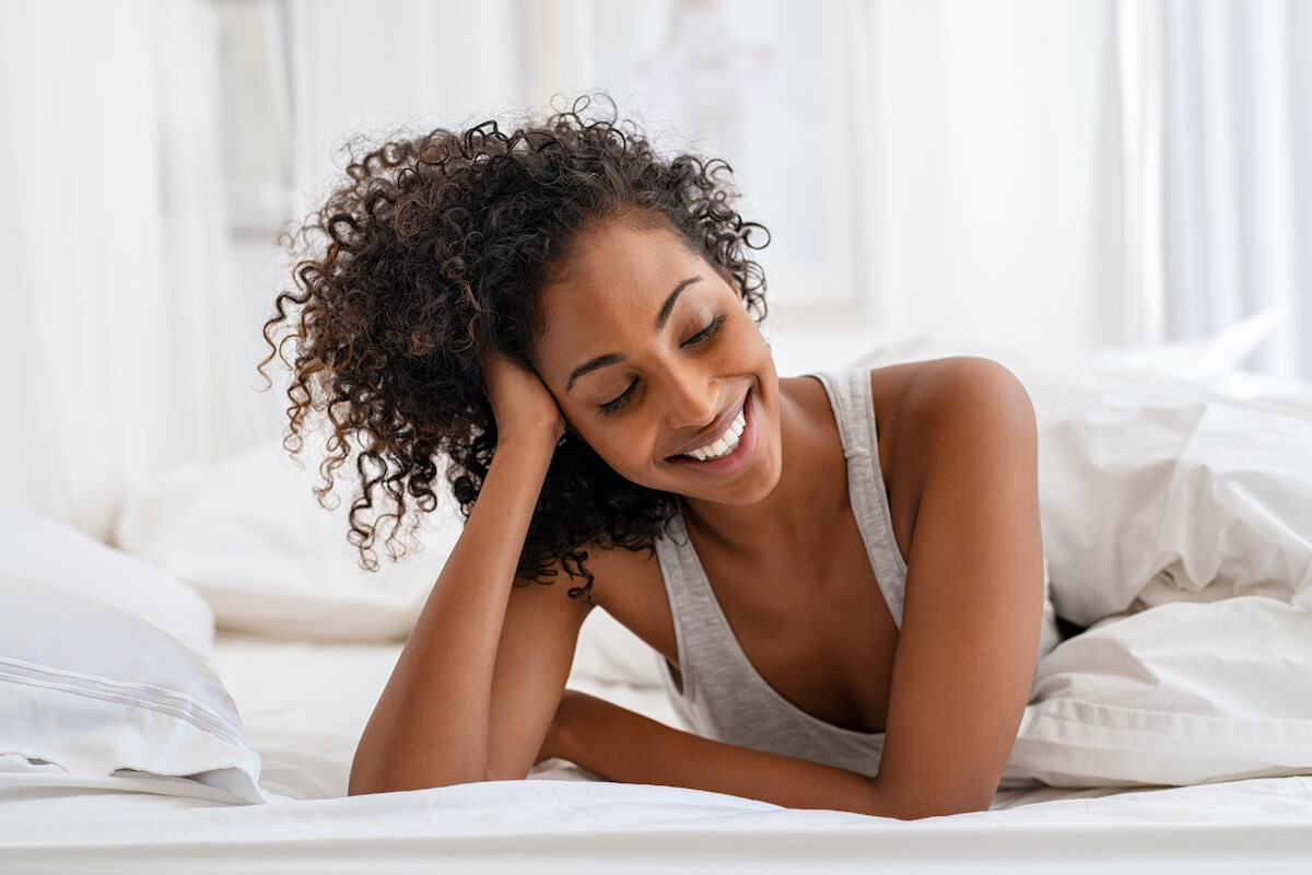 how to reset sleep schedule: smiling woman laying on her bed