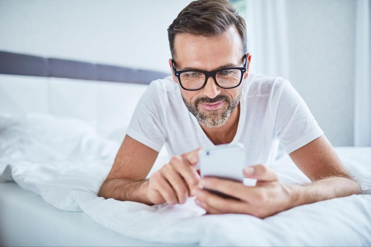 Smiling man using his phone while lying on his stomach in bed