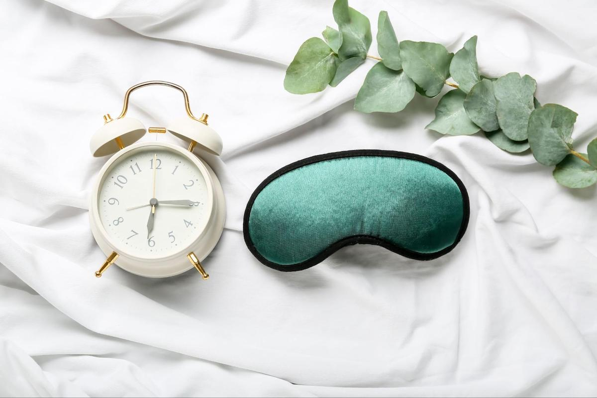 how to make yourself tired: white alarm clock and a green eye mask
