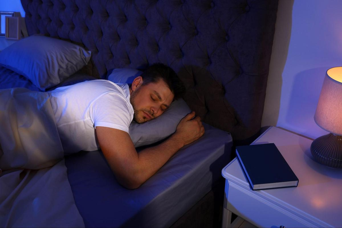 when should i wake up: man sleeping soundly in his bed