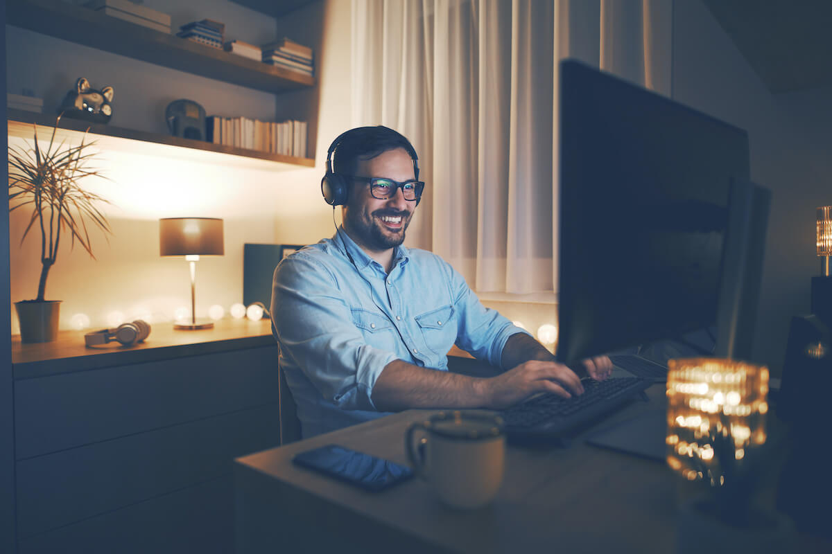 how to become a morning person: happy man working on his computer