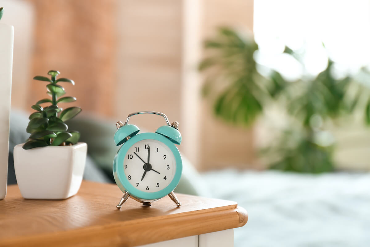 how to become a morning person: alarm clock on a bedside table