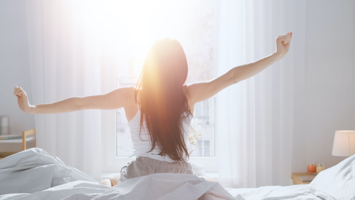bedtime routine: Woman stretching while looking out the window
