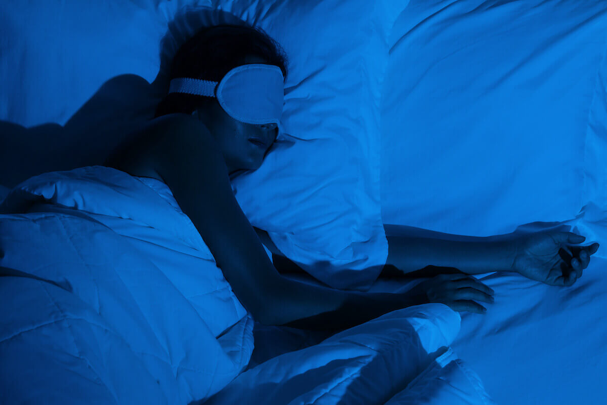 how long does melatonin last: person sleeping with an eye mask on