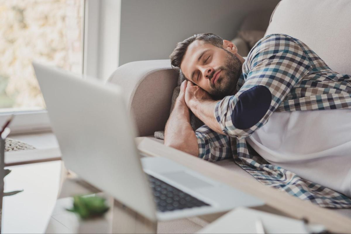 Man sleeping on his couch with his laptop open on the coffee table