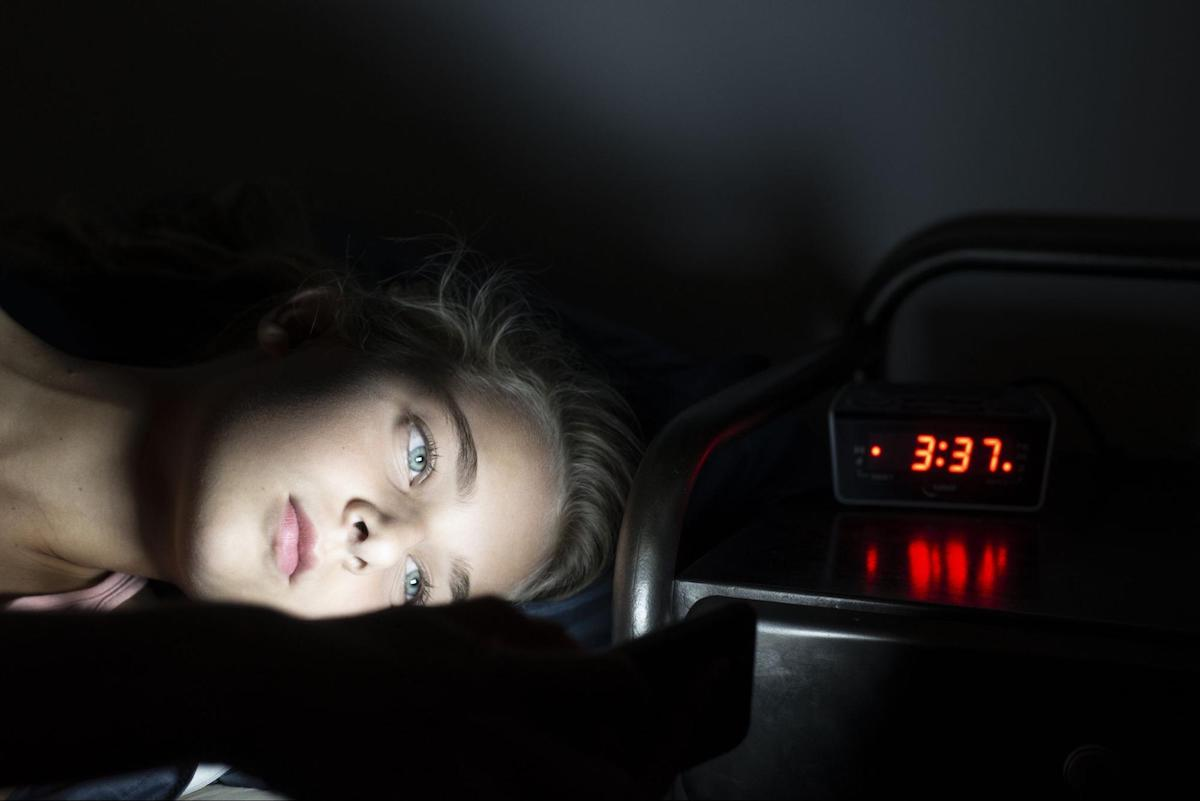 reset circadian rhythm: woman using her mobile phone in the dark
