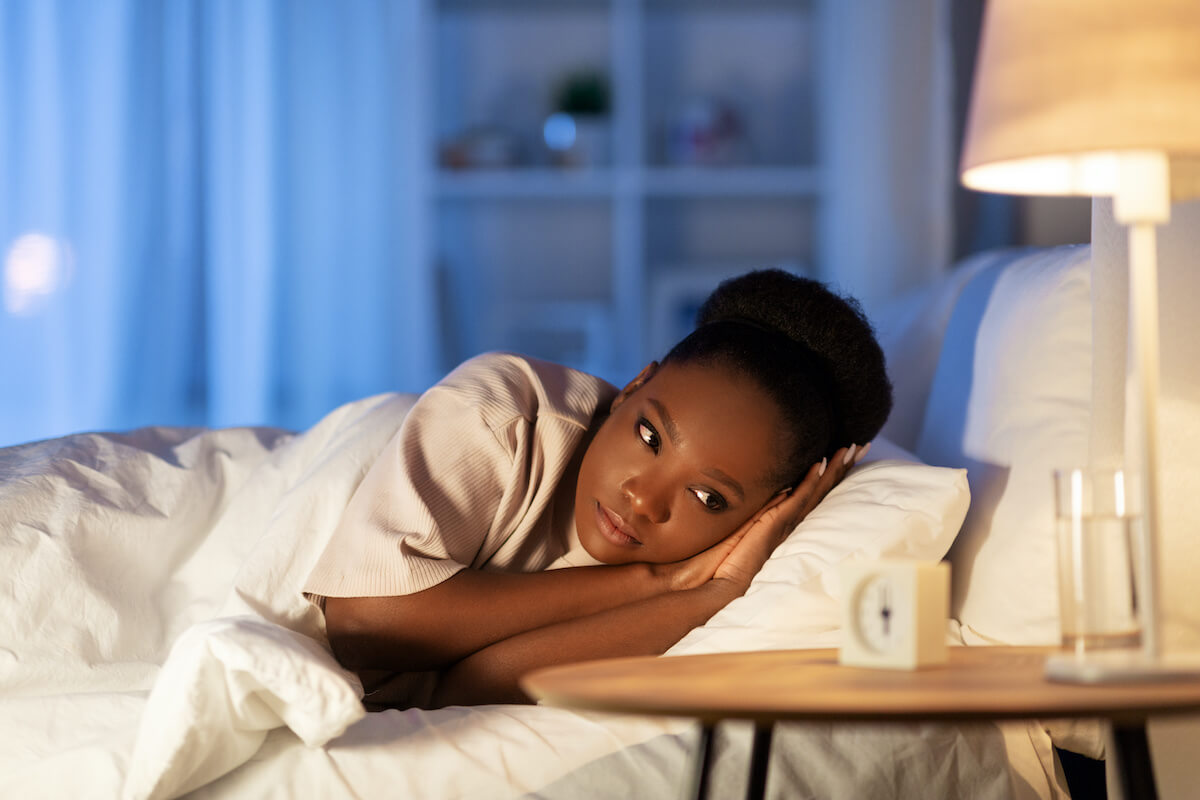 sleepy all the time: woman lying in her bed and looking at her clock