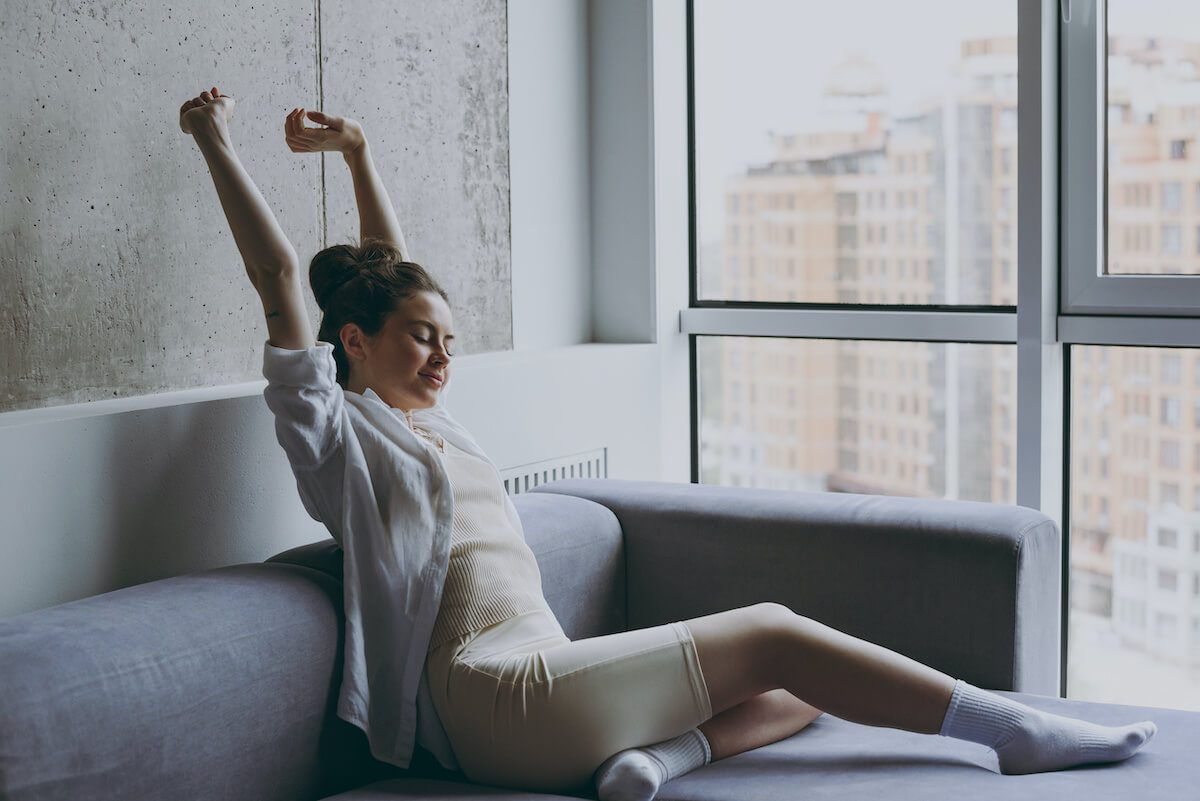 sleepy all the time: woman stretching while on her couch
