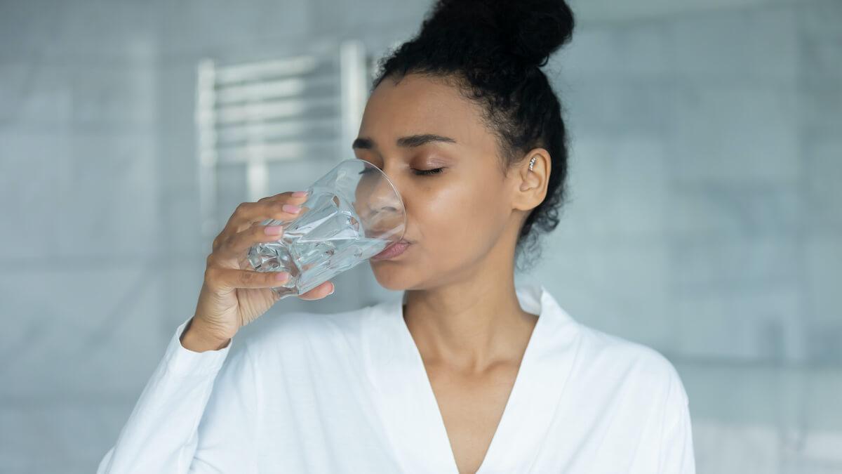 sleep supplements: woman drinking water