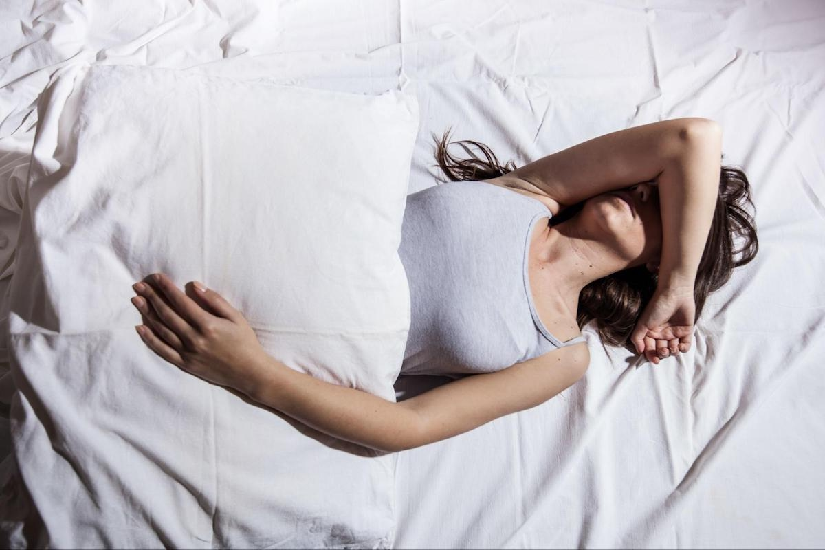 how to calm anxiety at night: woman sleeping soundly while covering her face with her arm