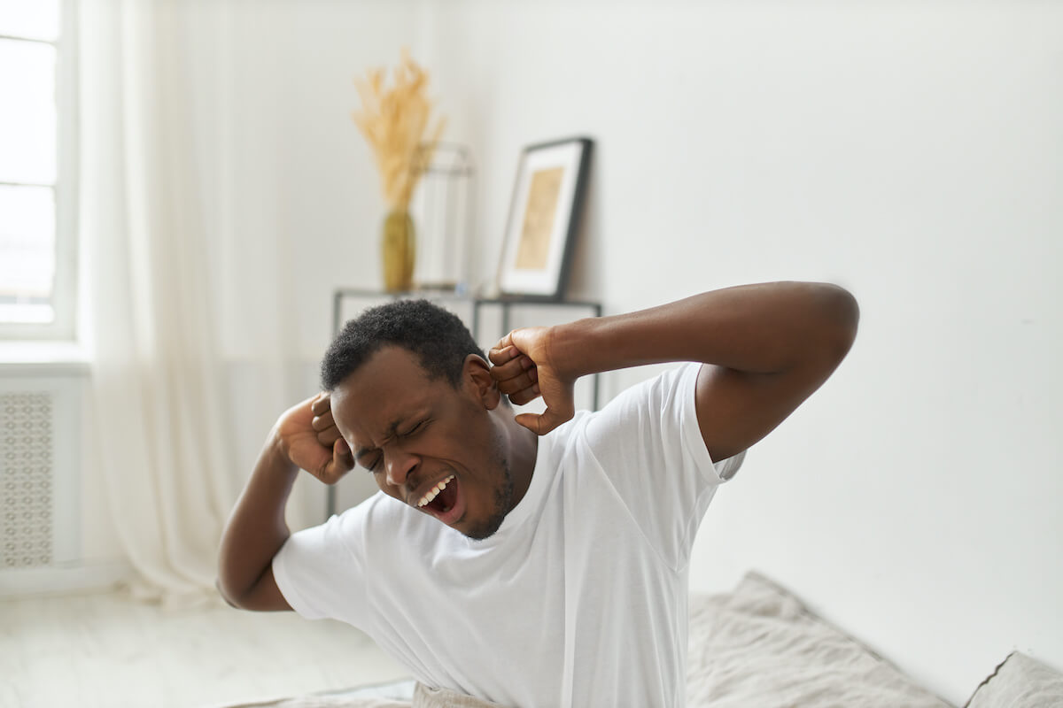 Sleeping in: man waking up and yawning