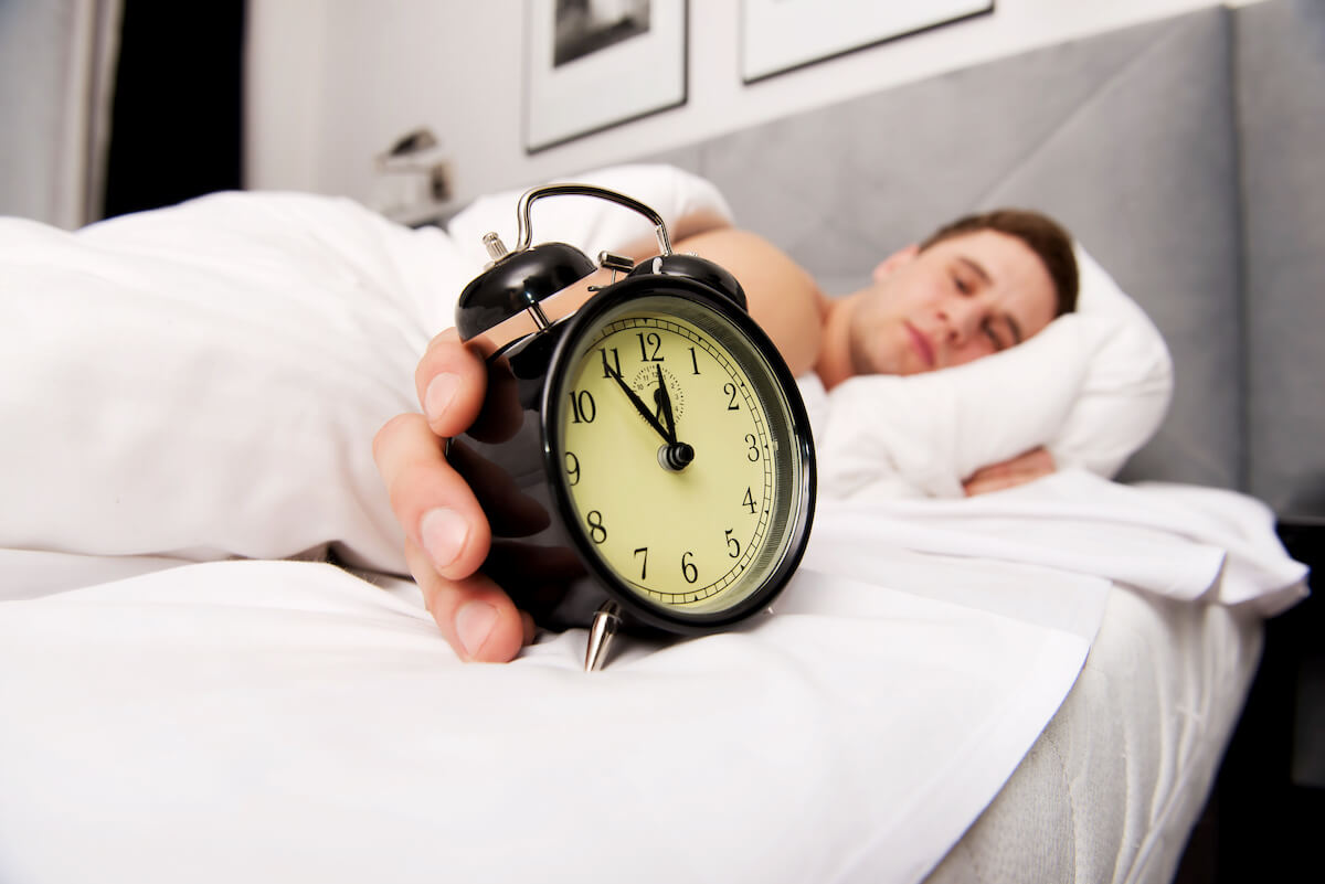 Sleeping in: man in bed, holding an alarm clock