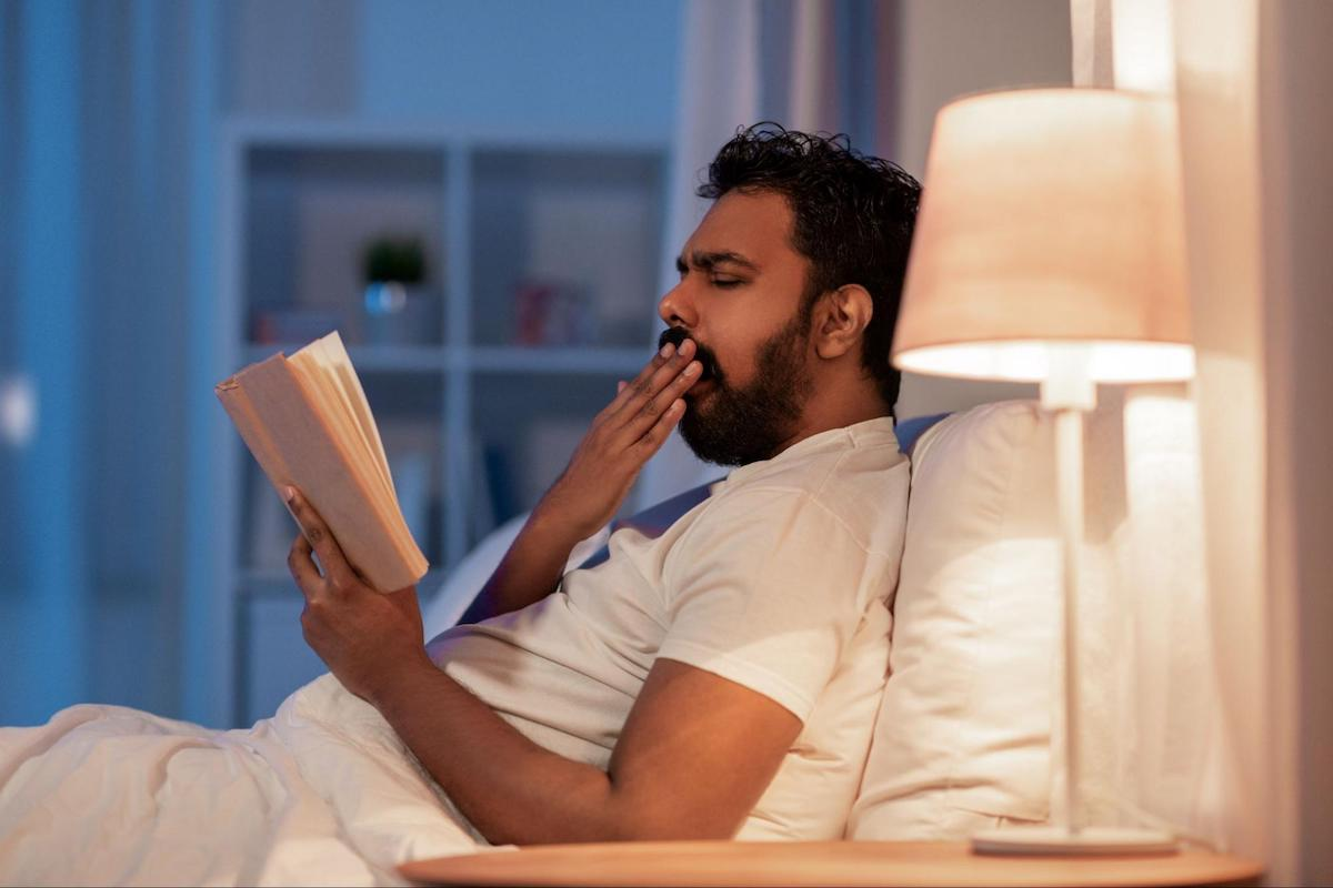 Man yawning while reading a book in bed