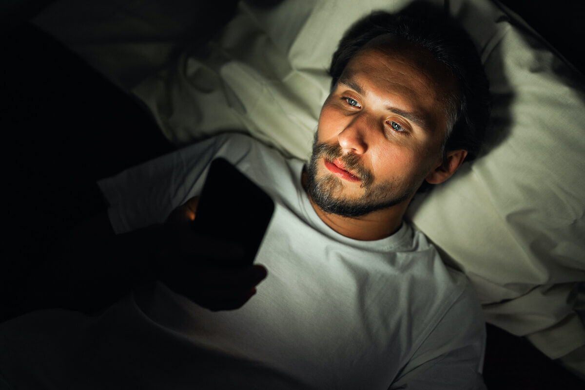 Do blue light glasses work: man in bed checking his phone