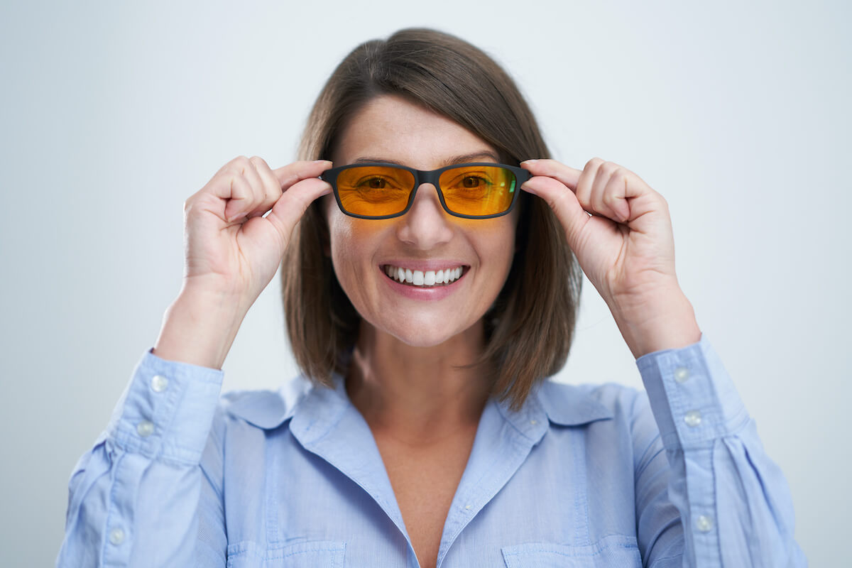 Do blue light glasses work: Smiling woman wearing blue-light blocking glasses