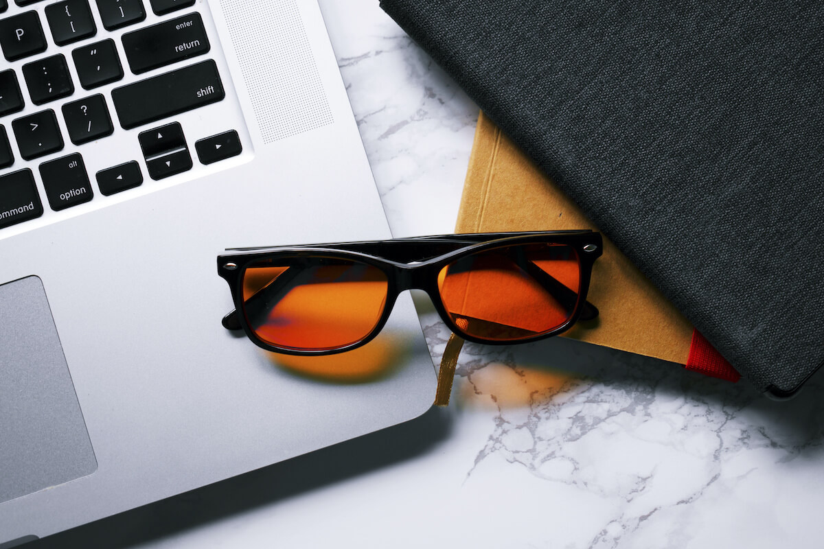 Blue-light blocking glasses by a laptop and notebooks