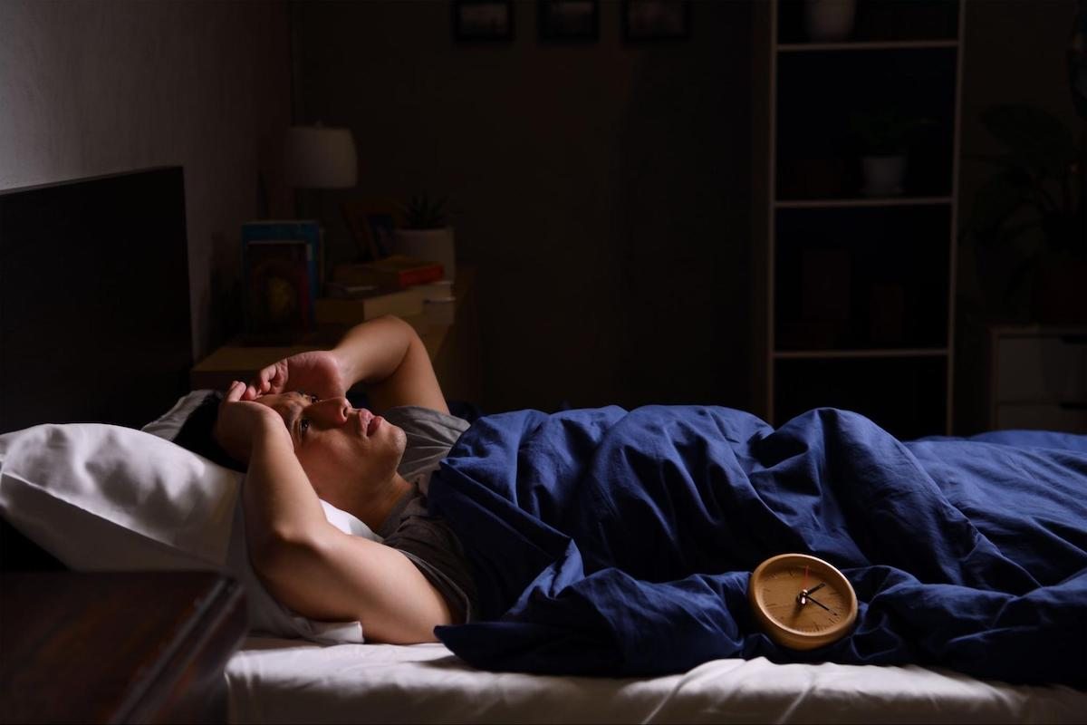Waking up with headaches: person lying in bed with a headache