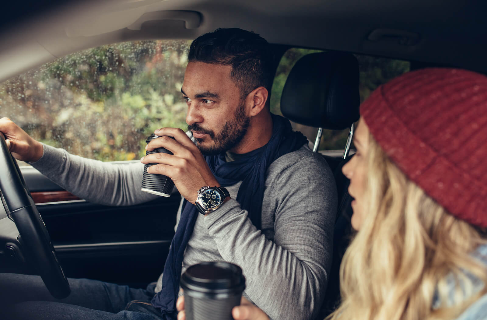 Couple drinking coffee in the car