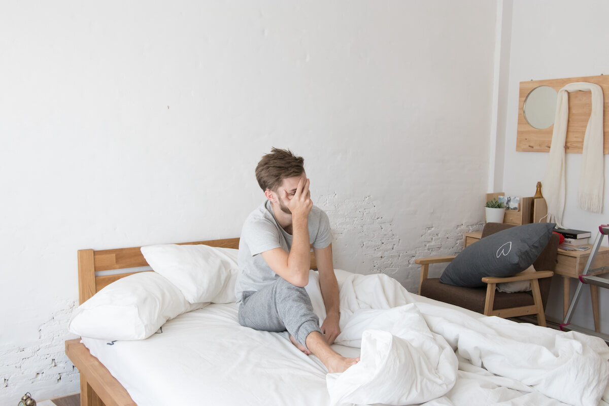 Drinking water before bed: man sitting on his bed, covering his face