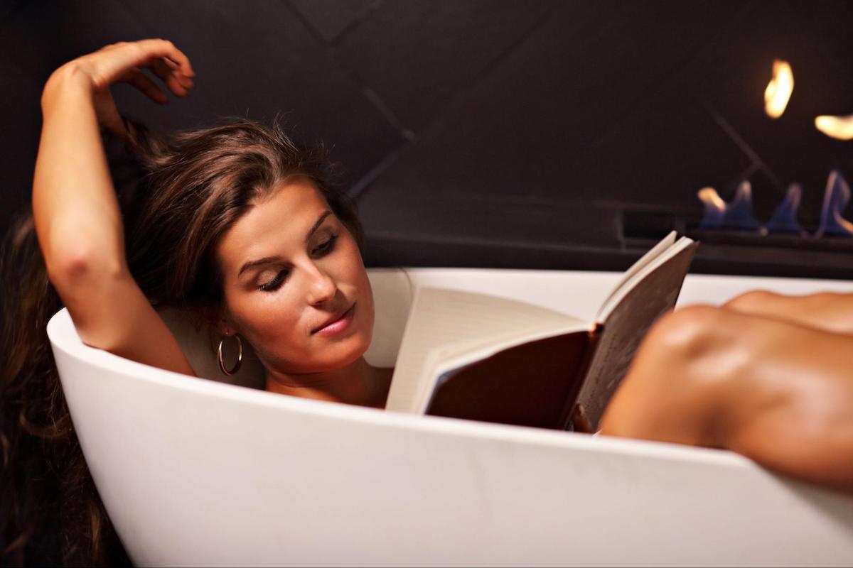 Woman in a bathtub reading a book